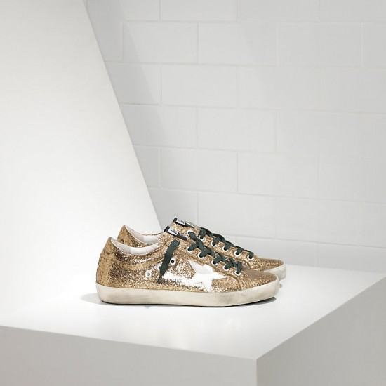 Women Golden Goose superstar in gold glitter emerald sneaker