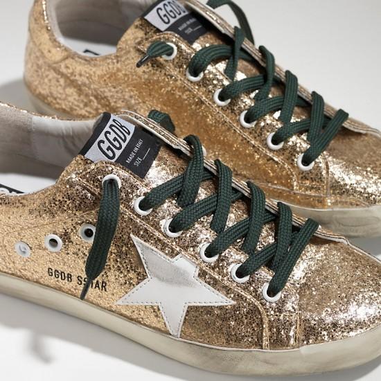 Women Golden Goose superstar in gold glitter emerald sneaker