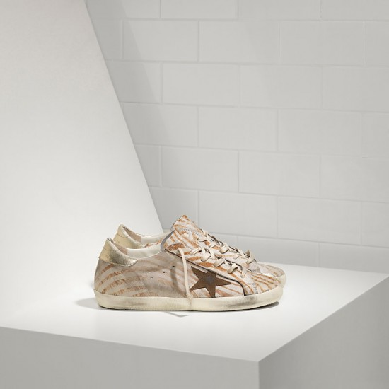 Women Golden Goose superstar in gold zebra sneaker